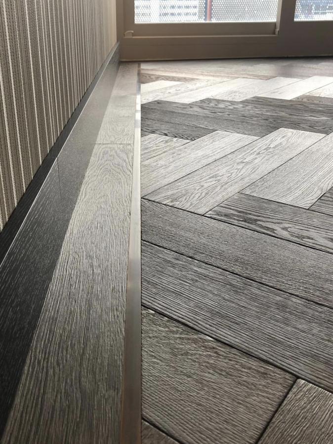 Деревянный пол ручной работы из инженерного жженого Темного Американского Ореха Елочка с металлическими вставками. Амстердам